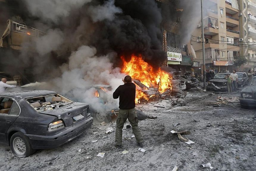 Lebanese men try to extinguish fire from burning cars following an explosion on Jan 21, 2014 in Haret Hreik, a south Beirut neighbourhood considered a stronghold of the Lebanese Shi'ite movement Hezbollah. Two people were killed in the apparent suici