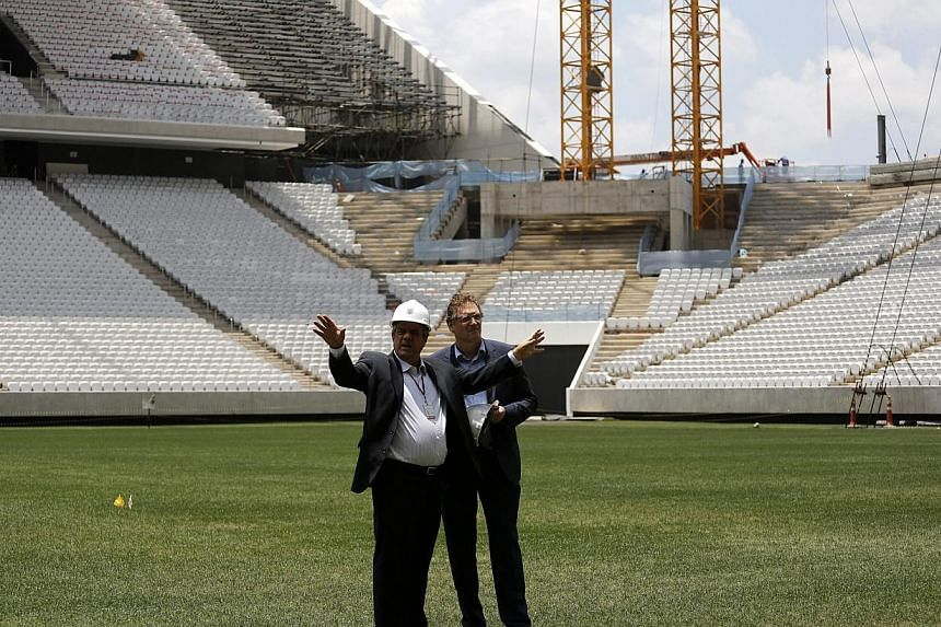 FIFA Secretary General Jerome Valcke (right) talks with an engineer during a visit to the site of the Arena Corinthians stadium, which is being prepared to host 2014 World Cup matches, in Sao Paulo Jan 20, 2014.Valcke said on Monday he was conf