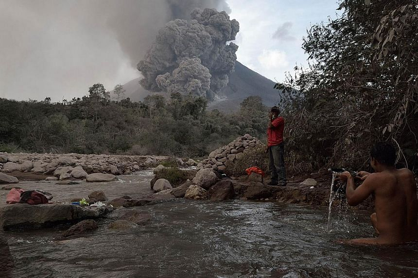 A villager in Karo district bathes in the river while Mt Sinabung erupts spewing lava and giant ash clouds on Jan 21, 2014. Mt Sinabung has forced more than 28,000 people to flee their homes and is one of 129 active volcanoes in Indonesia that stradd