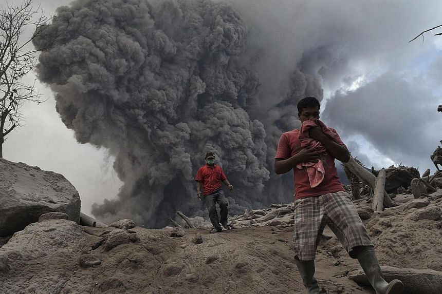 Villagers run on ash during the eruption of Mt Sinabung volcano near Gamber village in Karo district, in Indonesia's North Sumatra province, Jan 21, 2014. More than 28,000 villagers have been evacuated since authorities raised the alert status for th