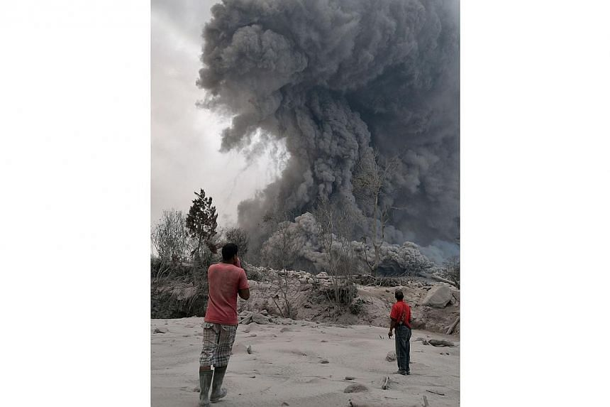 Two villagers watch as Mt Sinabung erupts spewing lava and giant ash clouds in Karo on Jan 21, 2014. Mt Sinabung has forced more than 28,000 people to flee their homes and is one of 129 active volcanoes in Indonesia that straddle major tectonic fault