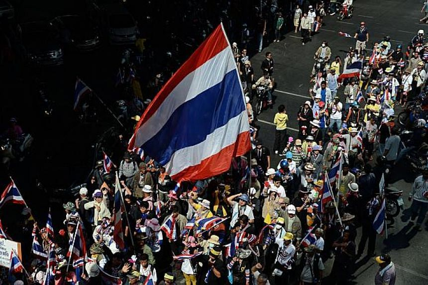 Thai anti-government protesters wave national flags as they march as part of their ongoing rallies in downtown Bangkok on Jan 21, 2014. The Ministry of Foreign Affairs has advised Singaporeans who wish to travel to Bangkok to avoid large gatherings a