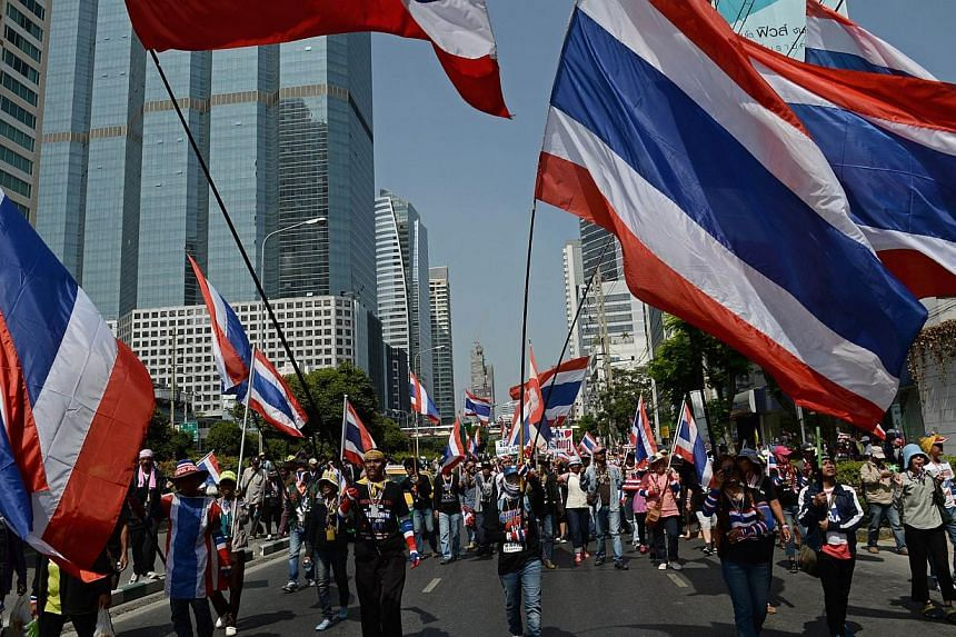 Thai anti-government protesters wave national flags as they march as part of their ongoing rallies in downtown Bangkok on Jan 21, 2014. The United States on Tuesday urged all sides in Thailand to show restraint and refrain from violence as the US all