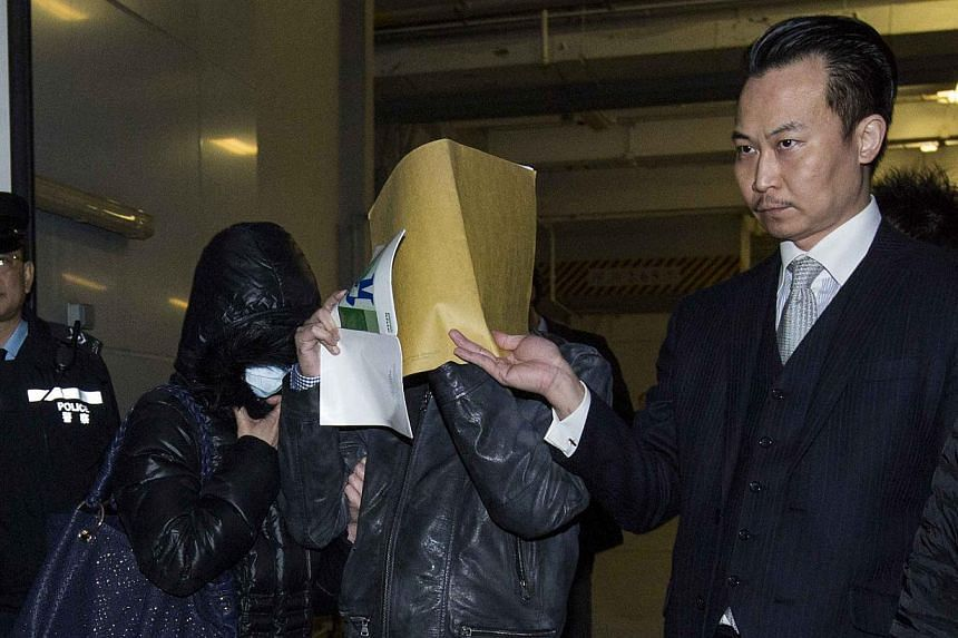 Law Wan-tung (with face mask), who has been charged with two counts of wounding, one count of common assault and three counts of criminal intimidation, stands next to her husband (2nd R) as they leave a court in Hong Kong January 22, 2014. Law, a Hon
