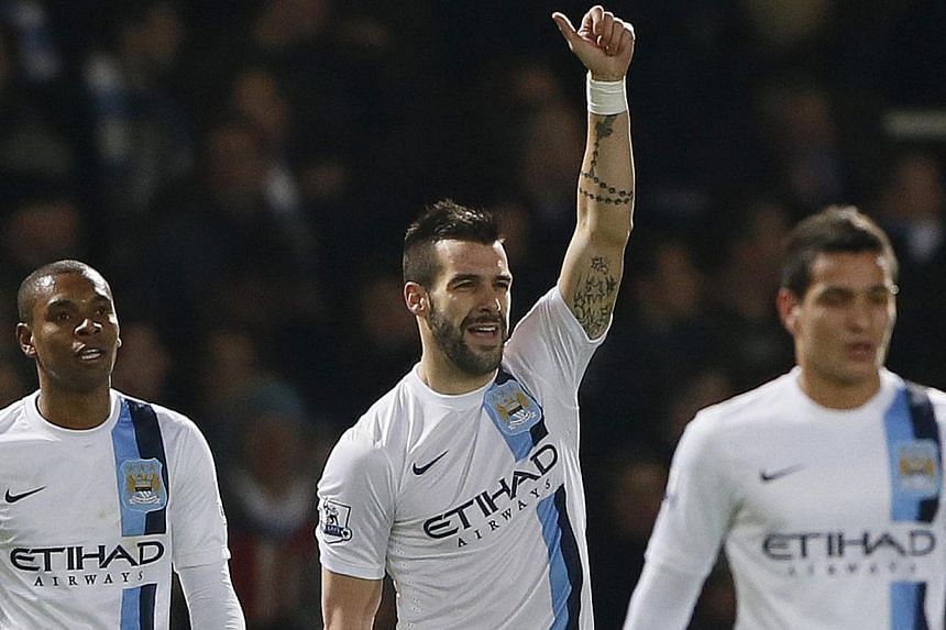 Manchester City's Alvaro Negredo (centre) celebrates scoring his second goal against West Ham United during their English League Cup semi-final second leg soccer match at Boleyn Ground in London Jan 21, 2014. Manchester City swept into the Leagu