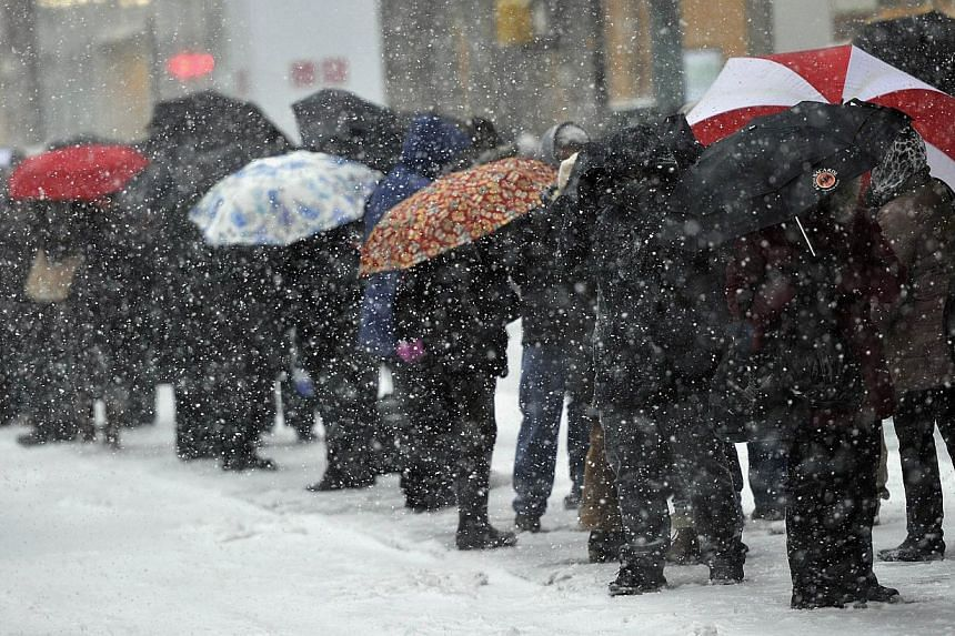 People wait at at bus stop on 5th Avenue in the snow as New Yorkers get hit with a winter storm in the North-east on Jan 21, 2014, that could bring up to 30cm of snow in the city. The northeastern US shivered amid heavy snowfall and far below av