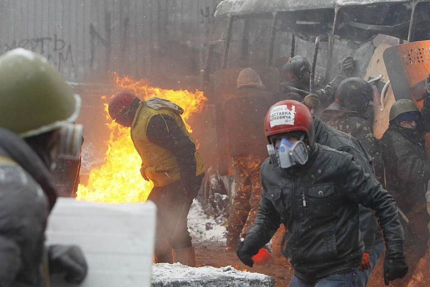 Pro-European protesters take cover behind a burnt bus during clashes with riot police in Kiev, on Jan 22, 2014.Two demonstrators were on Wendesday, Jan 22, 2014, reported killed in new anti-government unrest in the Ukrainian capital Kiev, infla