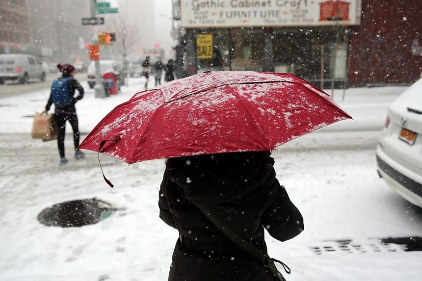 People walk in Manhattan during a snowstorm on Jan 21, 2014, in New York City. -- PHOTO: AFP