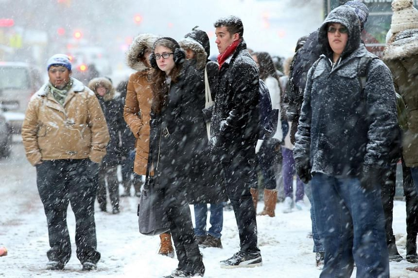 People wait for a delayed bus during a snowstorm on Jan 21, 2014, in New York City. -- PHOTO: AFP