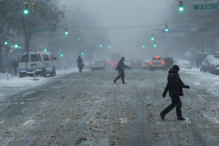 People walk across a street in Manhattan during a snowstorm on Jan 21, 2014, in New York City. -- PHOTO: AFP