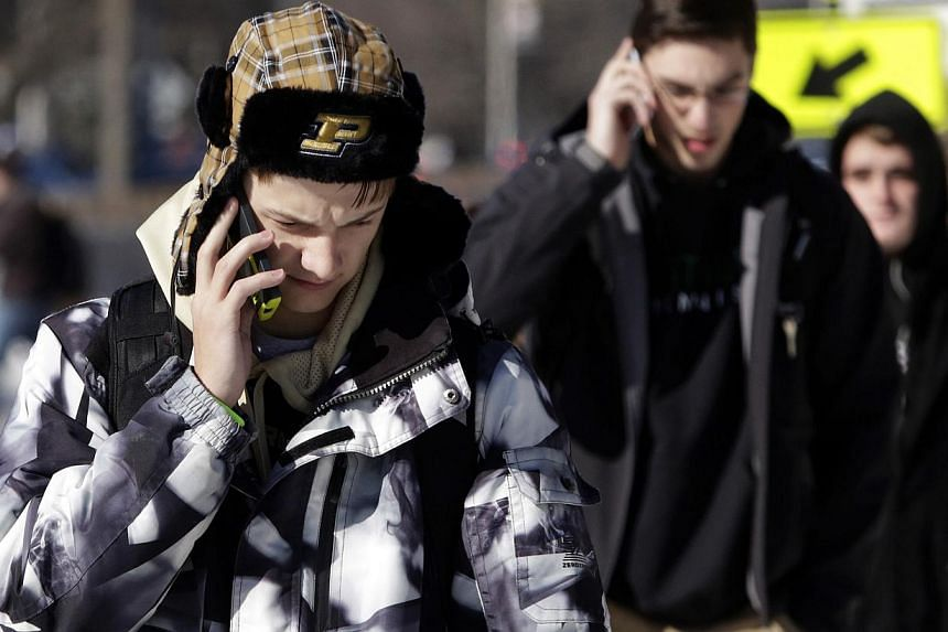 Students talk on their mobile phones after a campus lockdown was lifted at Purdue University in West Lafayette, Indiana, on Jan 21, 2014. One person is dead and one suspect in custody after a shooting at the university in what appeared to be a target
