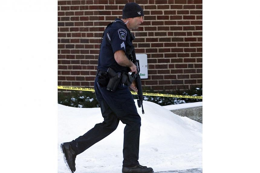 An officer walks with a gun at Purdue University in West Lafayette, Indiana, on Jan 21, 2014. One person is dead and one suspect in custody after a shooting at the university in what appeared to be a targeted attack at a specific person, according to