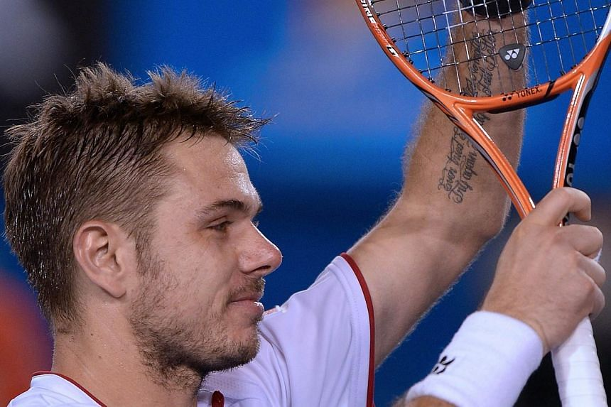 Switzerland's Stanislas Wawrinka celebrates after victory in his men's singles match against Serbia's Novak Djokovic on day nine at the 2014 Australian Open tennis tournament in Melbourne on Jan 21, 2014. -- PHOTO: AFP