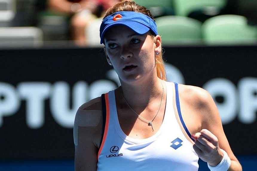 Agnieszka Radwanska of Poland reacts after hitting a shot against Victoria Azarenka of Belarus during their women's singles match on day 10 of the 2014 Australian Open tennis tournament in Melbourne on Jan 22, 2014. -- PHOTO: AFP