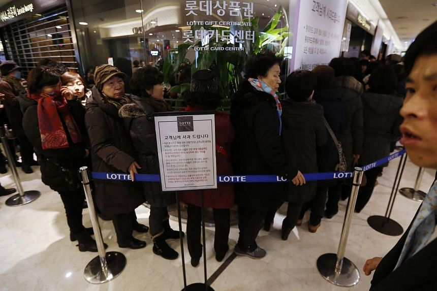 An apology (centre) to customers is displayed as customers wait in a line to apply for their credit cards to be reissued at Lotte Card's main office in Seoul on Tuesday, Jan 21, 2014.South Korean regulators on Wednesday vowed tougher penalties