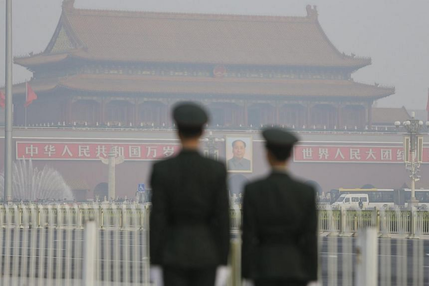 Paramilitary police officers stand guard near Tiananmen Gate on a hazy day in Beijing, on Oct 28, 2013.The city of Beijing will ban the construction of new oil refining, steel, cement and thermal power plants as well as the expansion of existing proj