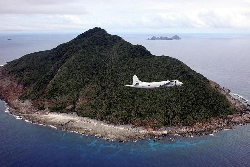 This photo taken on Oct 13, 2011 shows a P-3C patrol plane of Japanese Maritime Self-Defense Force flying over the disputed islets known as the Senkaku islands in Japan and Diaoyu islands in China, in the East China Sea. Japan took its campaign