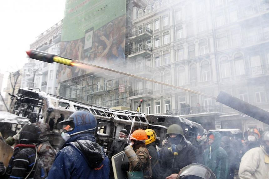 "Pro-European protesters launch a pyrotechnic pistol towards riot police during clashes in Kiev on Wednesday, Jan 22, 2014. Ukrainian Prime Minister Mykola Azarov said on Wednesday anti-government protests had brought ""terrorists"" on to the streets an"