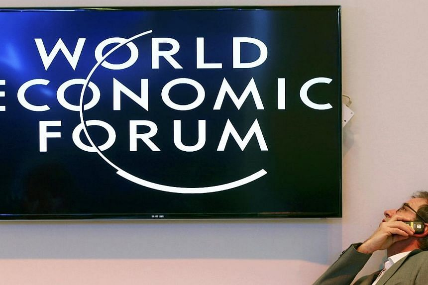 A participant speaks on his mobile phone between sessions during the annual meeting of the World Economic Forum (WEF) in Davos on Jan 22, 2014. -- PHOTO: REUTERS