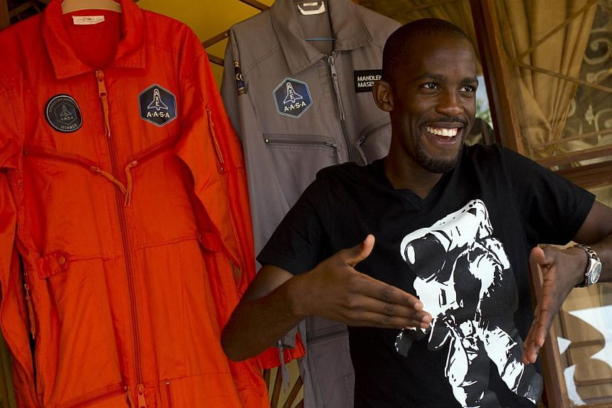 Mandla Maseko speaks to a journalist in front of two Nasa spacesuits in Mabopane, north of Pretoria, on Jan 9, 2014. Twenty-five-year-old Maseko has landed a coveted seat to fly 103km into space in 2015, after winning a competition organised by a Uni
