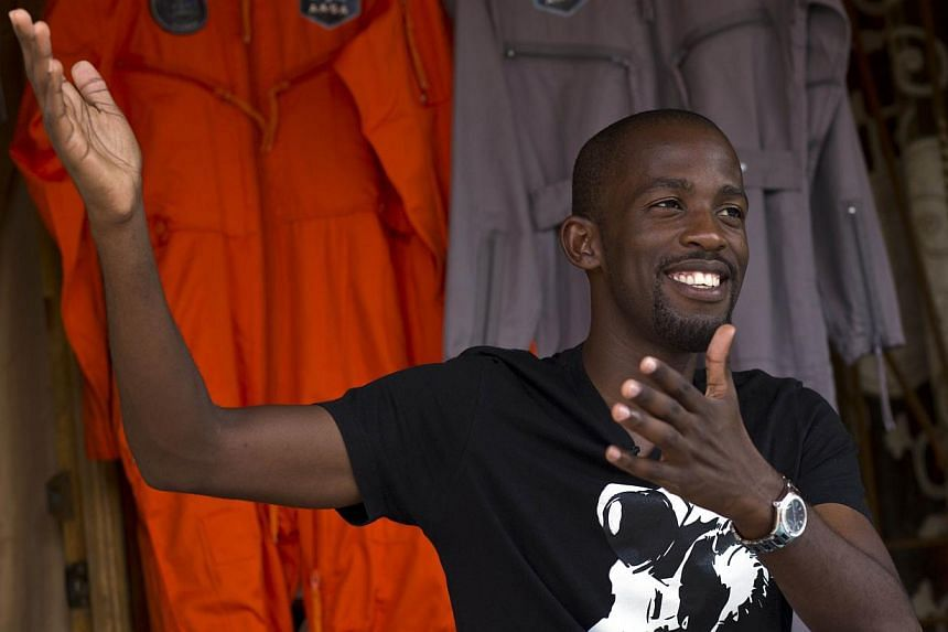 Mandla Maseko speaks to a journalist in front of two hanged Nasa spacesuits on Jan 9, 2014, in Mabopane, north of Pretoria. Maseko has landed a coveted seat to fly 103km into space in 2015, after winning a competition organised by a United States-bas