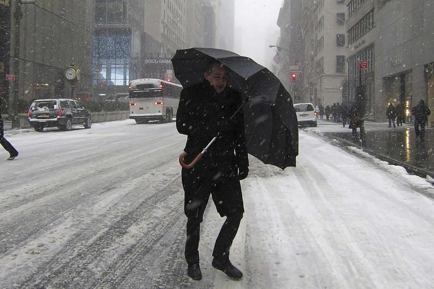 A man shields himself with an umbrella as he crosses 5th Avenue as snow falls in New York on Jan 21, 2014. A fast-moving winter storm forecast to dump as much as 30cm of snow on the north-eastern United States on Tuesday was expected to disrupt the e