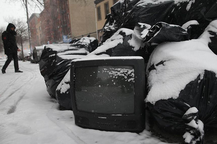 Garbage awaits pick-up during a snowstorm on Jan 21, 2014 in New York City. -- PHOTO: AFP