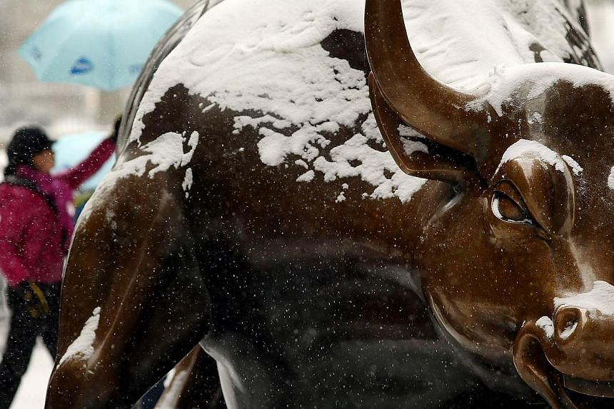 The Wall Street bull is dusted with snow during a snowstorm that is moving through the north-east on Jan 21, 2014 in New York City. -- PHOTO: AFP