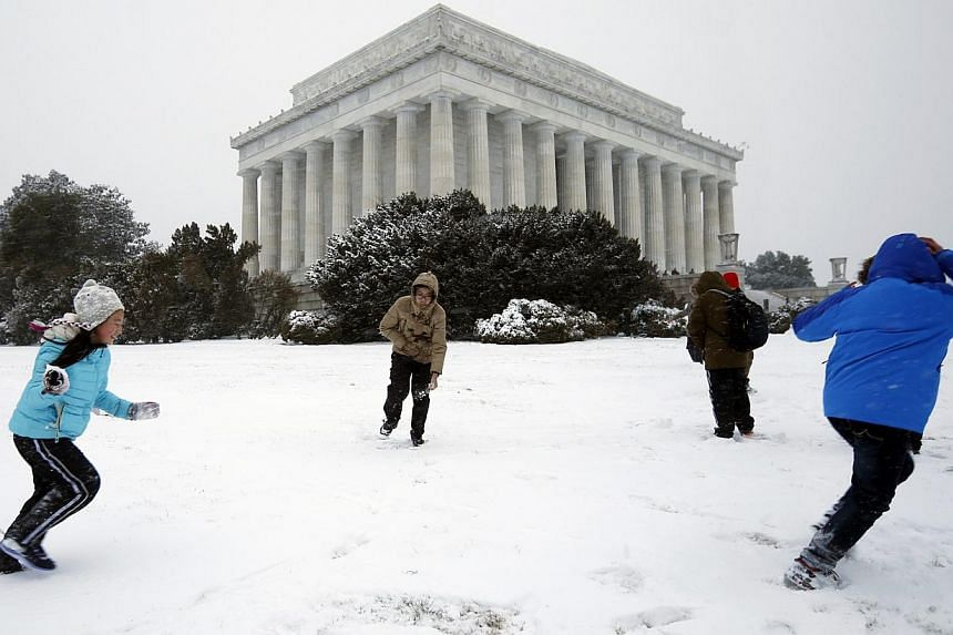 Children play in the snow at the Lincoln Memorial in Washington on Jan 21, 2014. -- PHOTO: REUTERS