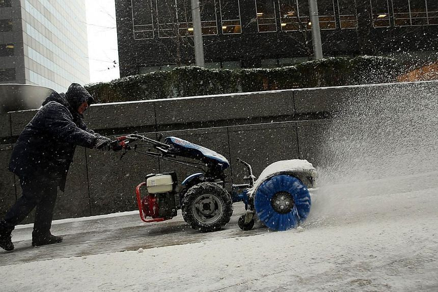 Sidewalks are cleared of snow and ice during a snowstorm that is moving through the north-east on Jan 21, 2014 in New York City. -- PHOTO: AFP