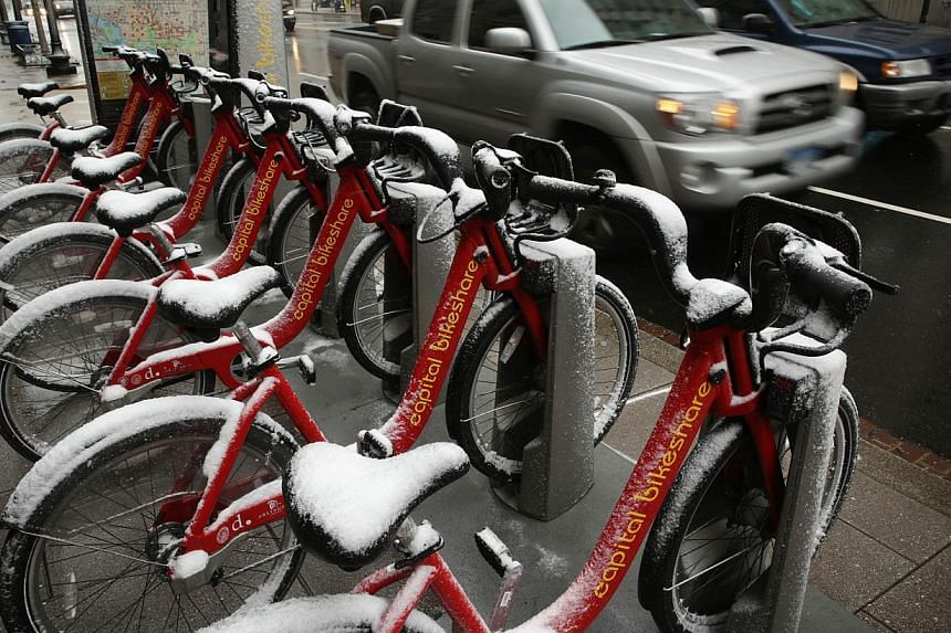 Capital Bikeshare bicycles are covered with snow at a loading dock on 14th Street on Jan 21, 2014 in Washington, DC. -- PHOTO: AFP