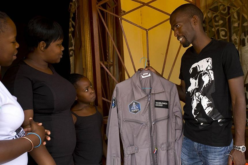 Mandla Maseko (right) shows his two Nasa spacesuits to his sisters on Jan 9, 2014, in Mabopane, north of Pretoria. No one in his family has ever stepped outside South Africa, but Maseko, a young township DJ, is set to rocket into space next year. --