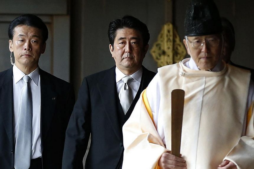 Japan's PM Abe is led by a Shinto priest as he visits Yasukuni shrine in Tokyo last Dec. -- PHOTO: REUTERS