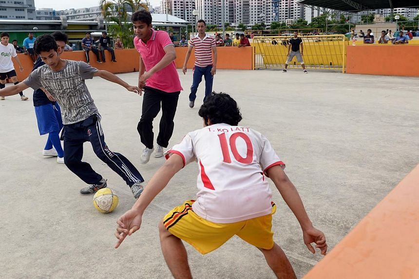 Workers playing street soccer at a recreation centre in Jurong West. There are plans to build more such leisure facilities to add to the four now in operation. -- ST FILE PHOTO