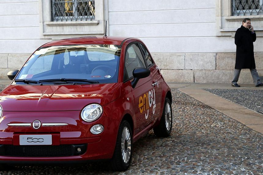A man walks near a red Fiat 500 car in downtown Milan, on Dec 16, 2013. Subcompact cars including the Fiat 500 and Honda Fit performed the worst of any vehicle segment so far in a tough new test that assesses what happens when the front corner o