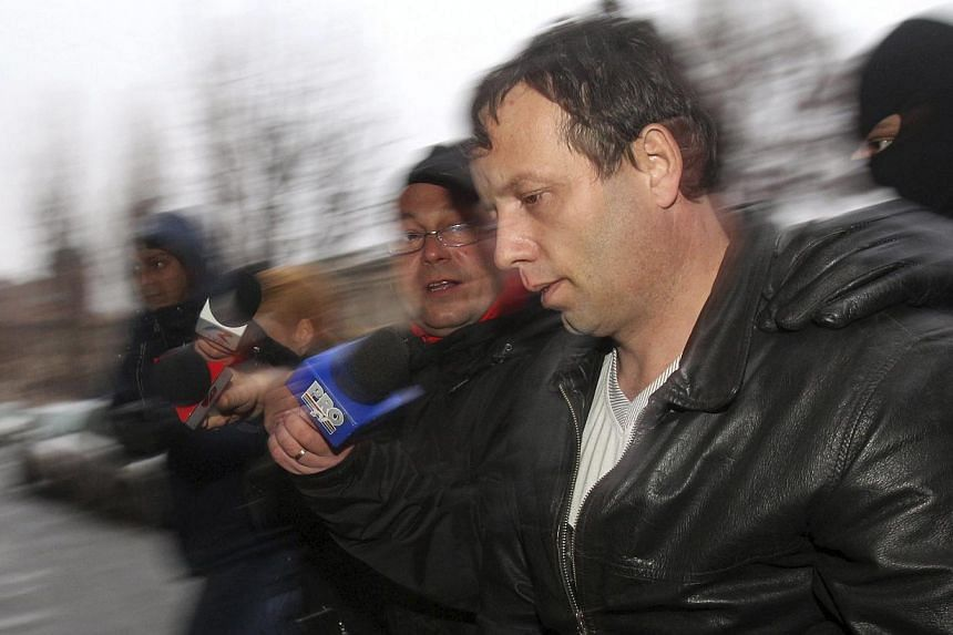 """Marcel Lazar Lehel, 40, is escorted by masked policemen in Bucharest, after being arrested in Arad, 550km west of Bucharest on Jan 22, 2014.Romanian authorities have arrested a man they suspect of being the hacker """"Guccifer"""", famous for breakin"""