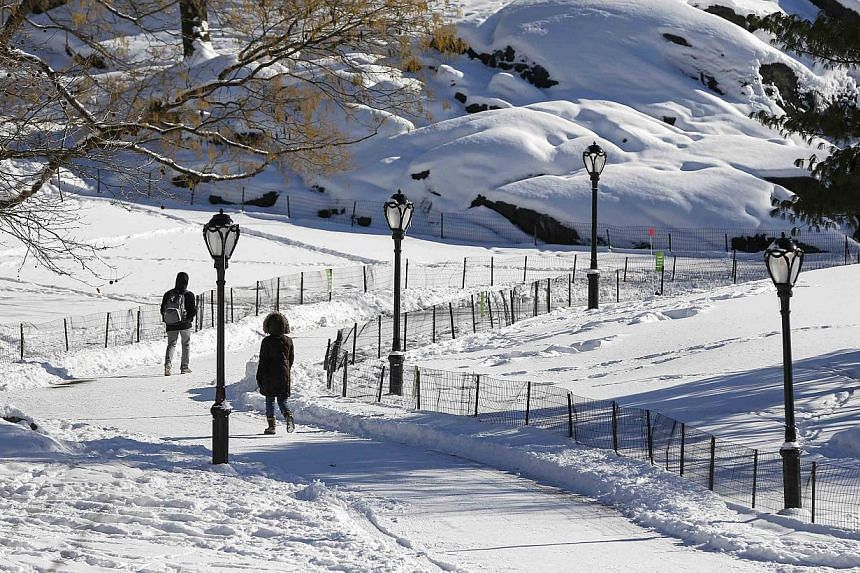 People walk through a snow covered Central Park in New York on Jan 22, 2014. Millions of American commuters braved miserable conditions across the East coast on Wednesday after a fierce storm dumped almost a foot of snow from the Mid-Atlantic to New