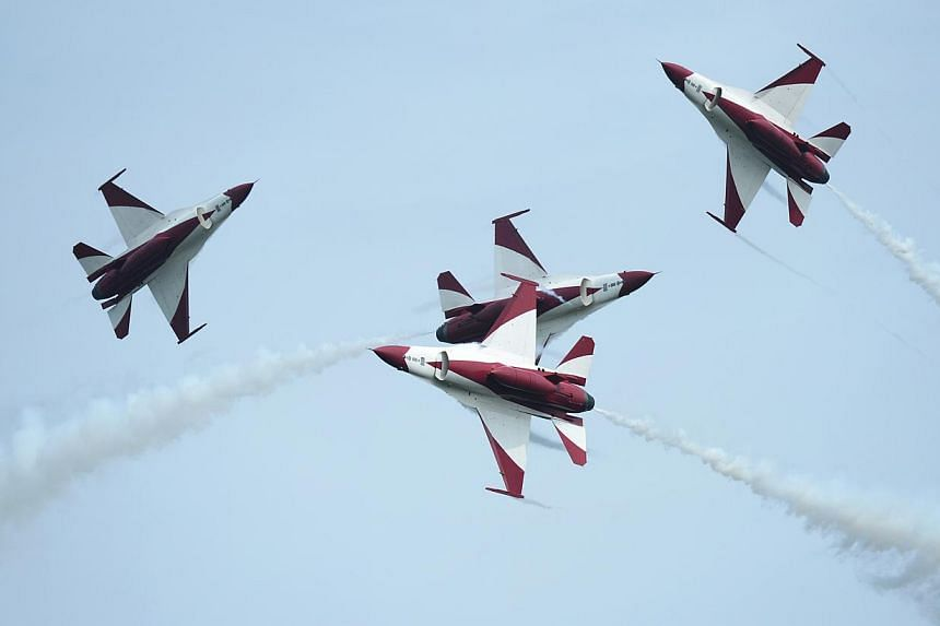 The Republic of Singapore Air Force (RSAF) aerobatics team, the Black Knights, perform a criss cross (new manoeuvre) during the media preview aerial display, on Jan 21, 2014. -- ST PHOTO: MARK CHEONG