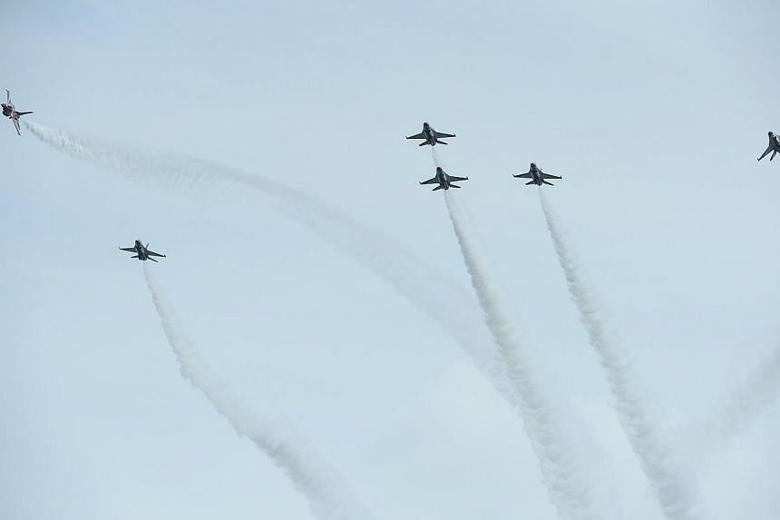The Republic of Singapore Air Force (RSAF) aerobatics team, the Black Knights, perform a twist and shout (new manoeuvre), during the media preview aerial display, on Jan 21, 2014. -- ST PHOTO: MARK CHEONG