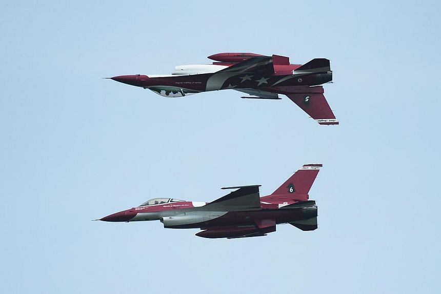 Two members of The Republic of Singapore Air Force (RSAF) aerobatics team, the Black Knights, perform a mirror pass during the media preview aerial display, on Jan 21, 2014. -- ST PHOTO: MARK CHEONG