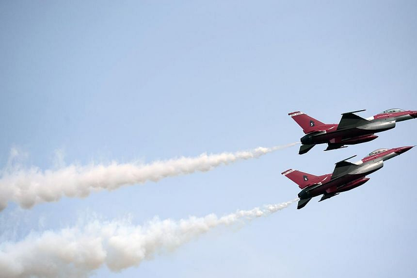 Two members of The Republic of Singapore Air Force (RSAF) aerobatics team, the Black Knights, perform a low and slow muscle climb during the media preview aerial display, on Jan 21, 2014. -- ST PHOTO: MARK CHEONG
