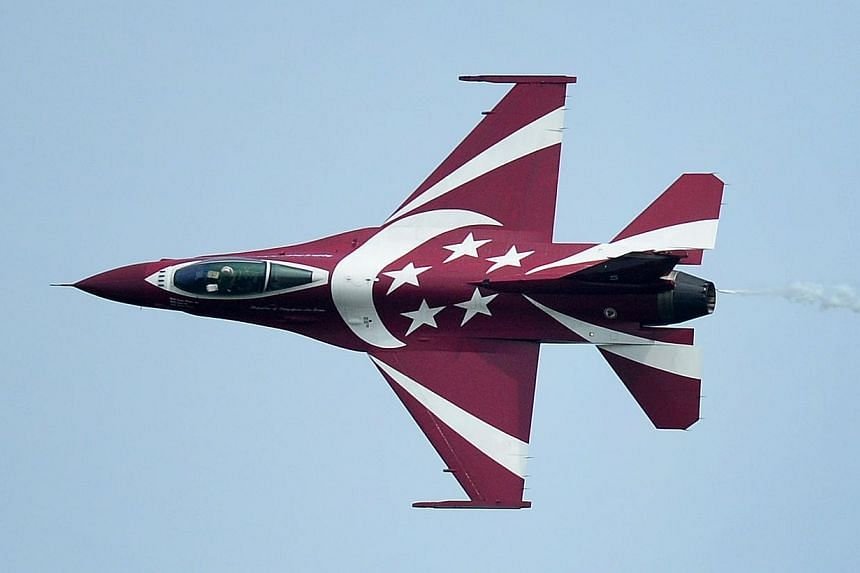 A member of The Republic of Singapore Air Force (RSAF) aerobatics team, the Black Knights, performs a knife edge pass, showcasing the aircraft's new paint scheme which incorporates the national symbols of the crescent moon and five stars, during the