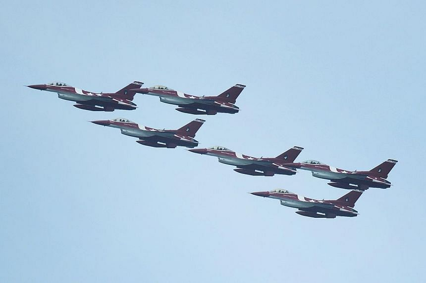 The Republic of Singapore Air Force (RSAF) aerobatics team, the Black Knights, perform a chevron loop during the media preview aerial display, on Jan 21, 2014. -- ST PHOTO: MARK CHEONG