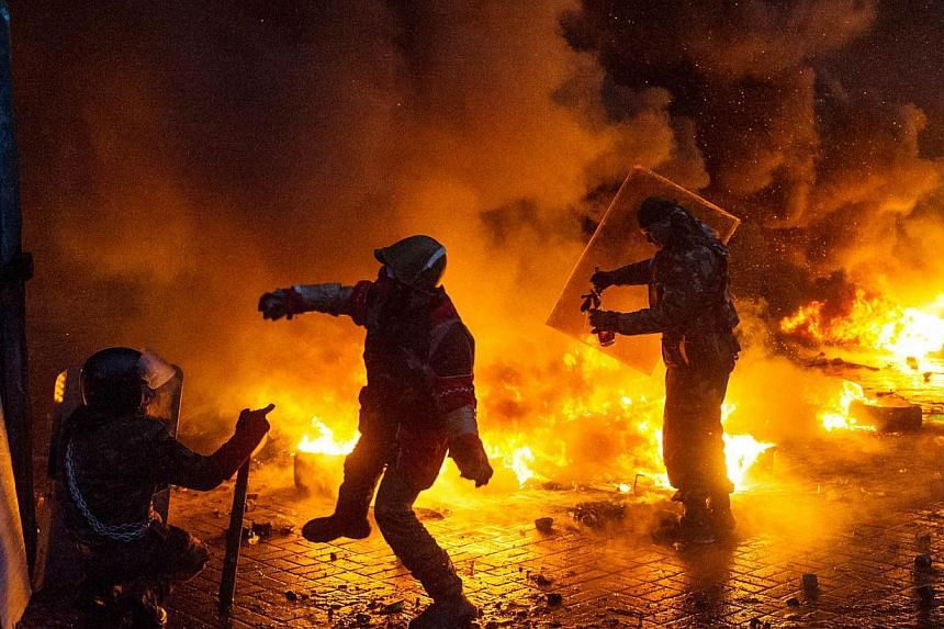 Protesters throw molotov cocktails at police during clashes in the centre of Kiev, on Jan 22, 2014. Ukraine's opposition threatened to go on the attack on Thursday, Jan 22, 2014, unless the government agreed to concessions to quell protests that