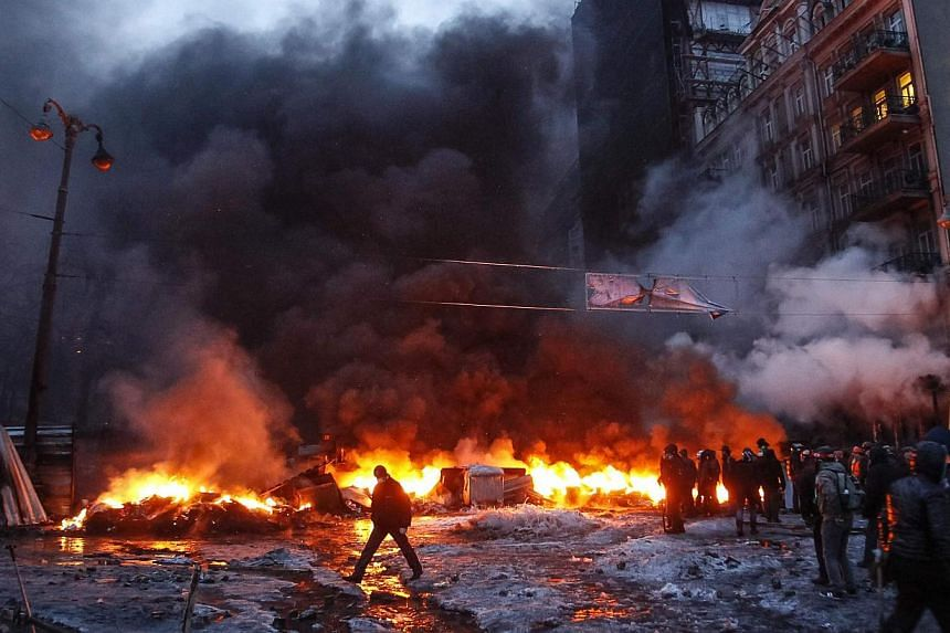 People walk near burning tires at the site of clashes of pro-European integration protesters with riot police in Kiev, on Jan 23, 2014. -- PHOTO: REUTERS