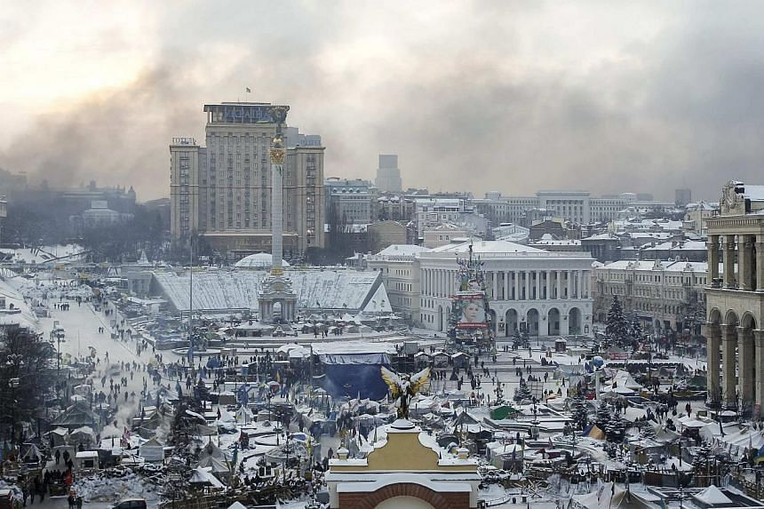 Smoke from burning tyres blanket Independence Square with pro-European integration protesters camped there in central Kiev, on Jan 23, 2014. -- PHOTO: REUTERS