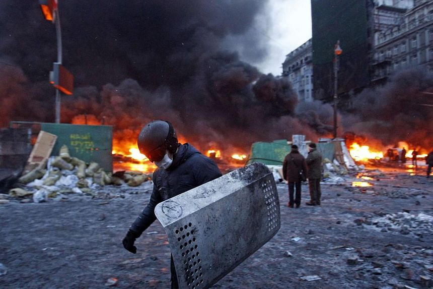 A pro-European protester carries a shield during street violence in Kiev, on Jan 23, 2014.-- PHOTO: REUTERS