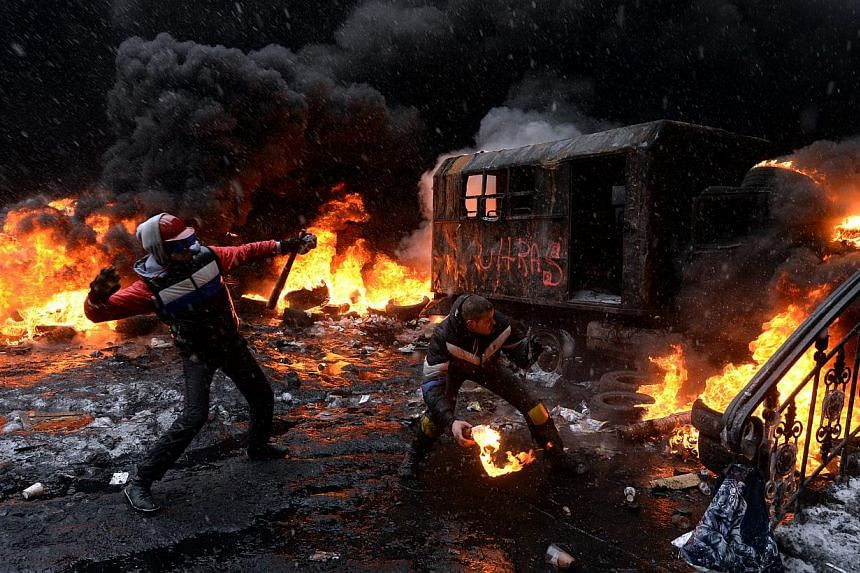 A protestor throws a molotov cocktail at riot police in the centre of Kiev, on Jan 22, 2014. -- PHOTO: AFP