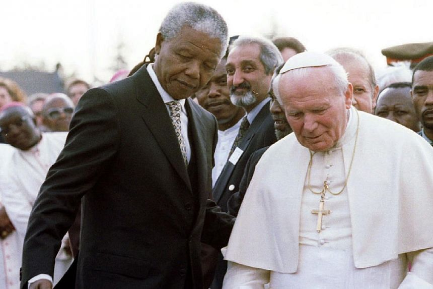 South African President Nelson Mandela (left) guides Pope John Paul II after they met at Johannesburg International Airport, at the start of the pope's first official visit to the country,on Sept 16, 1995.The personal secretary of late pope Joh