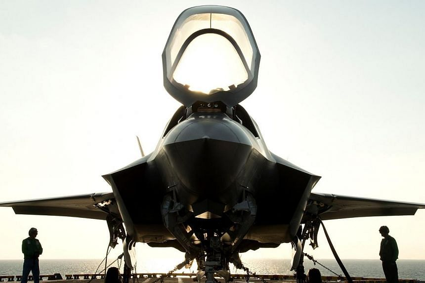 The flight deck crew secures an F-35B Lighting II aircraft aboard the amphibious assault ship USS Wasp following testing off the coast of North Carolina in this Aug 24, 2013 file photo.Britain may announce an order for 14 Lockheed Martin-built